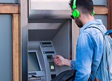 man getting money from cash machine