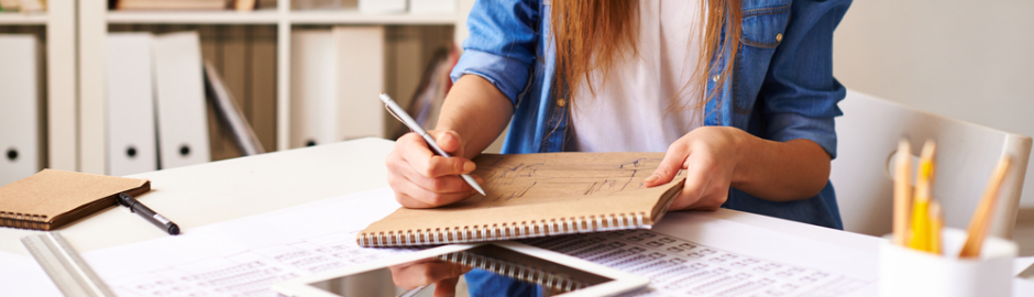Young woman writing and drawing in a notebook