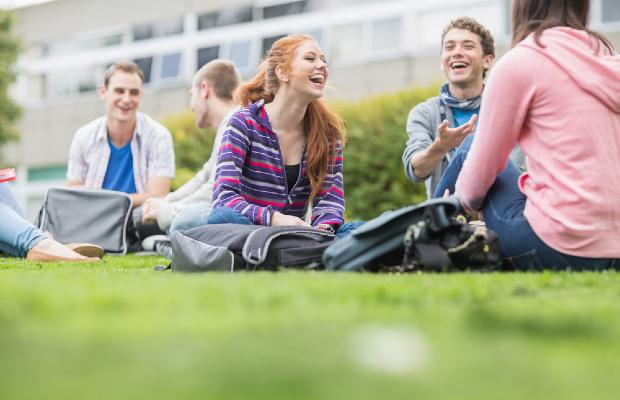 students sitting on grass together