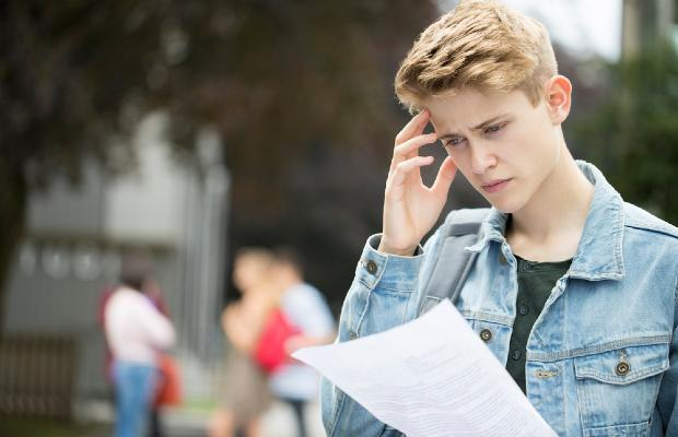 student reading exam results and looking stressed