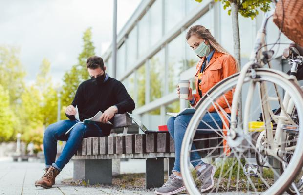 university students sitting outside with face masks on