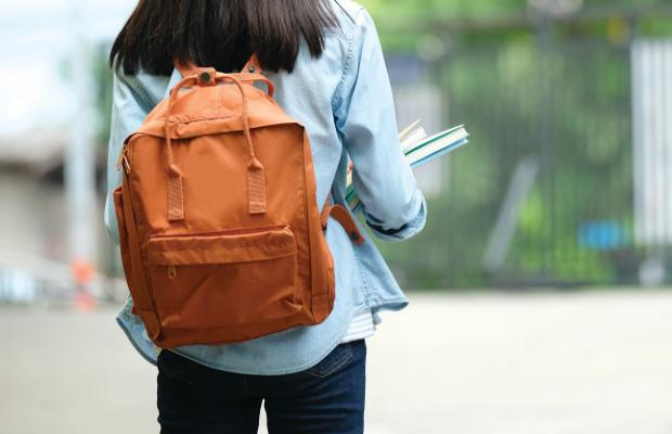 student wearing backpack and holding notebooks