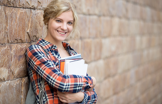 young female student holding books leaning against wall