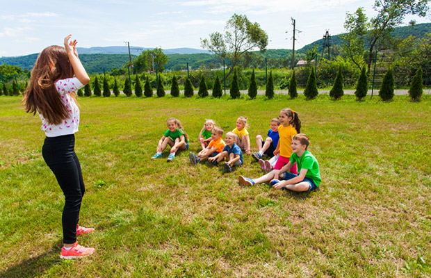 young woman leading activity at summer camp