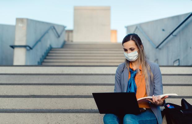 university student working on laptop and wearing a face mask