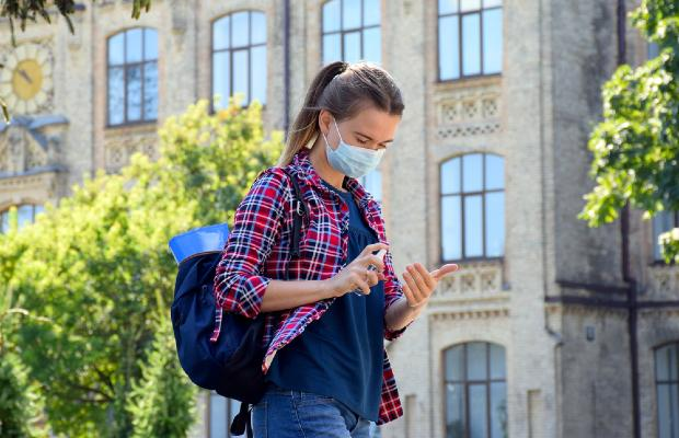 university student walking through campus and wearing a face mask