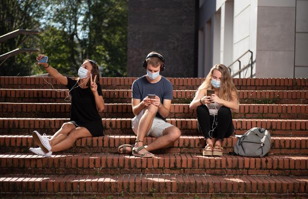 university students wearing face masks and sitting on steps outside