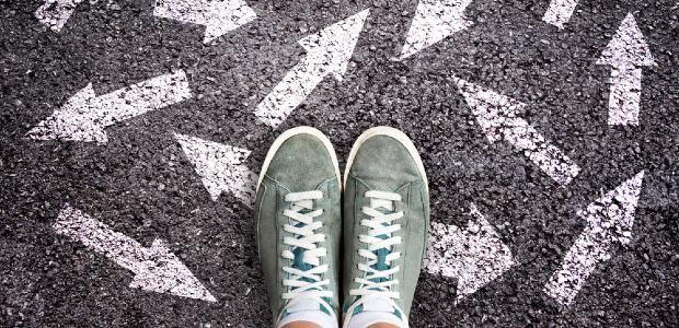 feet standing on arrows drawn in chalk on floor