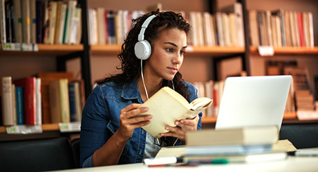student working in library with headphones on