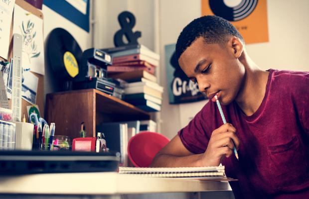 teenage boy writing in a notebook