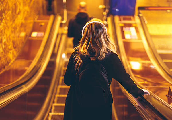Woman travelling up escalator