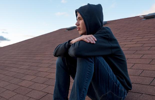 sad teen sitting on roof