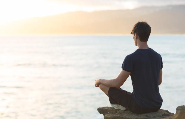 teen meditating on rock overlooking ocean