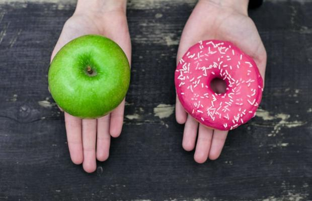 one hand holding an apple and one hand holding a donut
