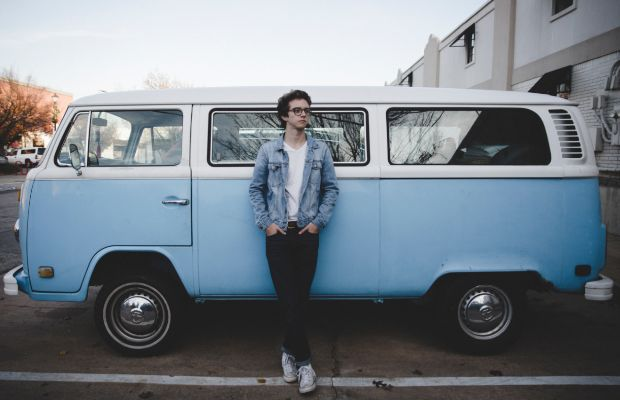 A teenager standing in front of a camper van