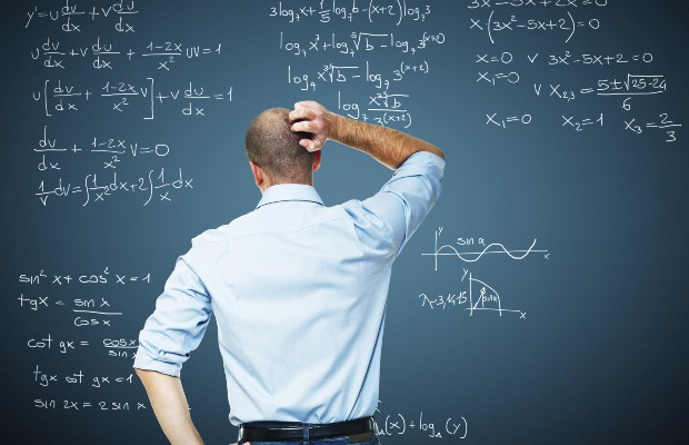 Teacher looking at calculations on a blackboard