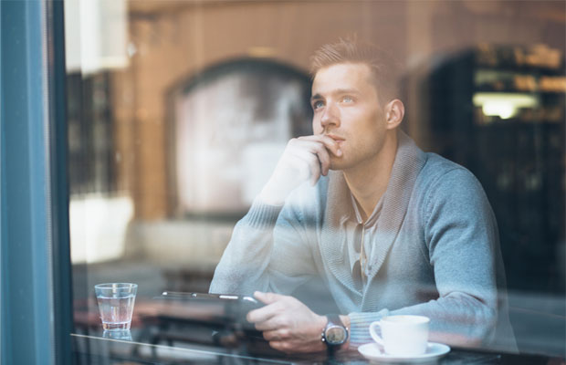 man looking out of a coffee shop window