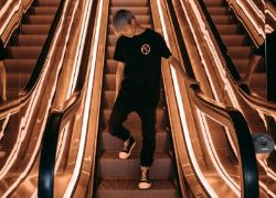 Cool young man standing on an escalator
