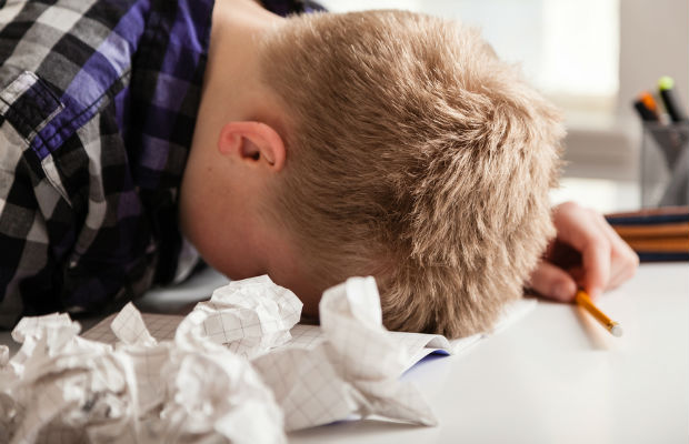 Young boy frustrated with studying with screwed up paper around him