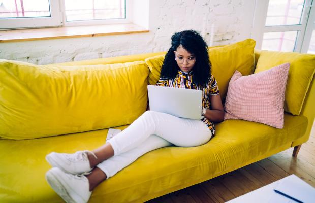 student sitting on sofa to work on laptop