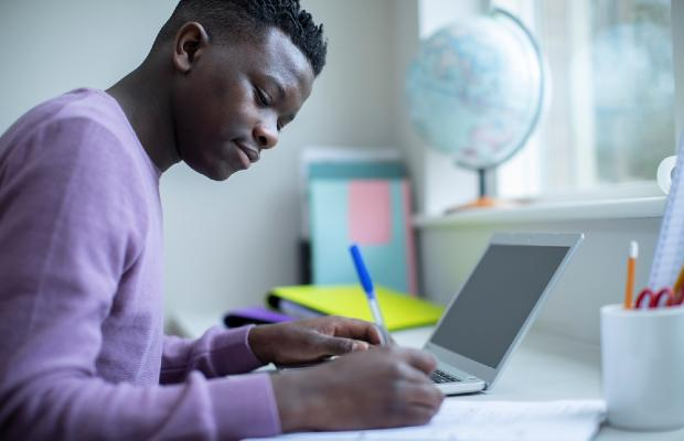 student making notes at laptop