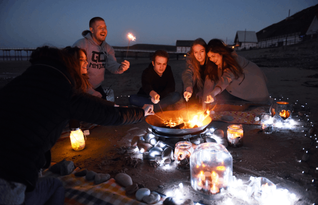 group of students around beach bonfire