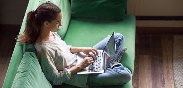 student sitting on sofa and working on laptop