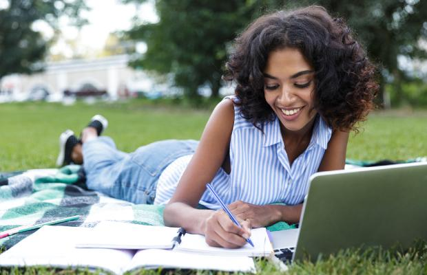 university student on laptop lying on the grass