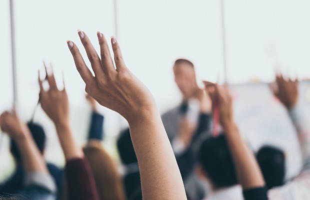 Students with raised hands to ask questions in class