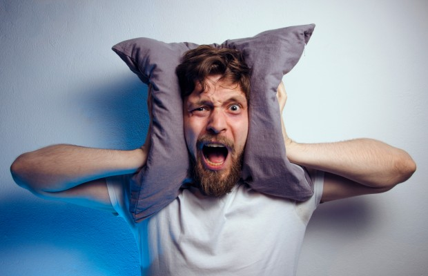 A man covers his ears with a pillow to block out noise late at night