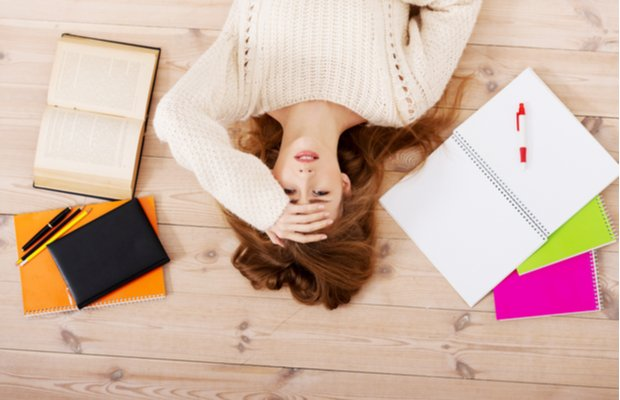 A girl lies on the floor surrounded by school books looking overwhelmed