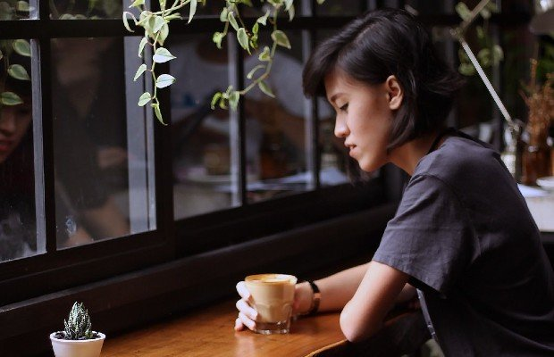 a woman in a coffee shop looking thoughtful