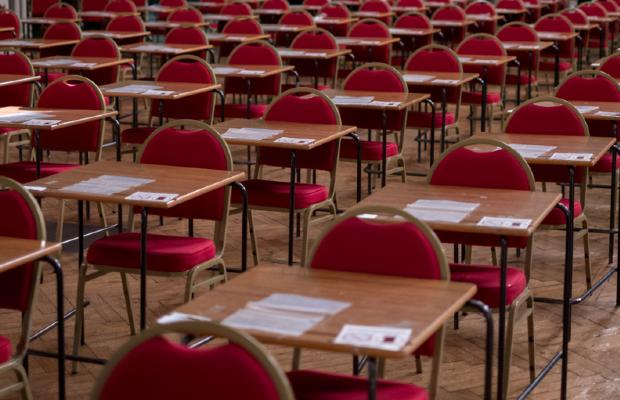 empty exam hall with papers laid out on the tables