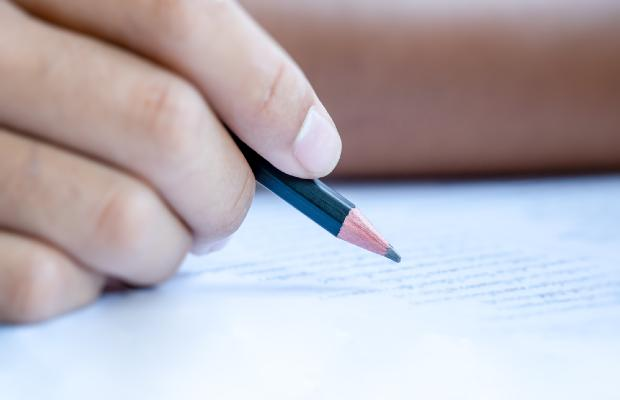 close-up of hand writing exam paper