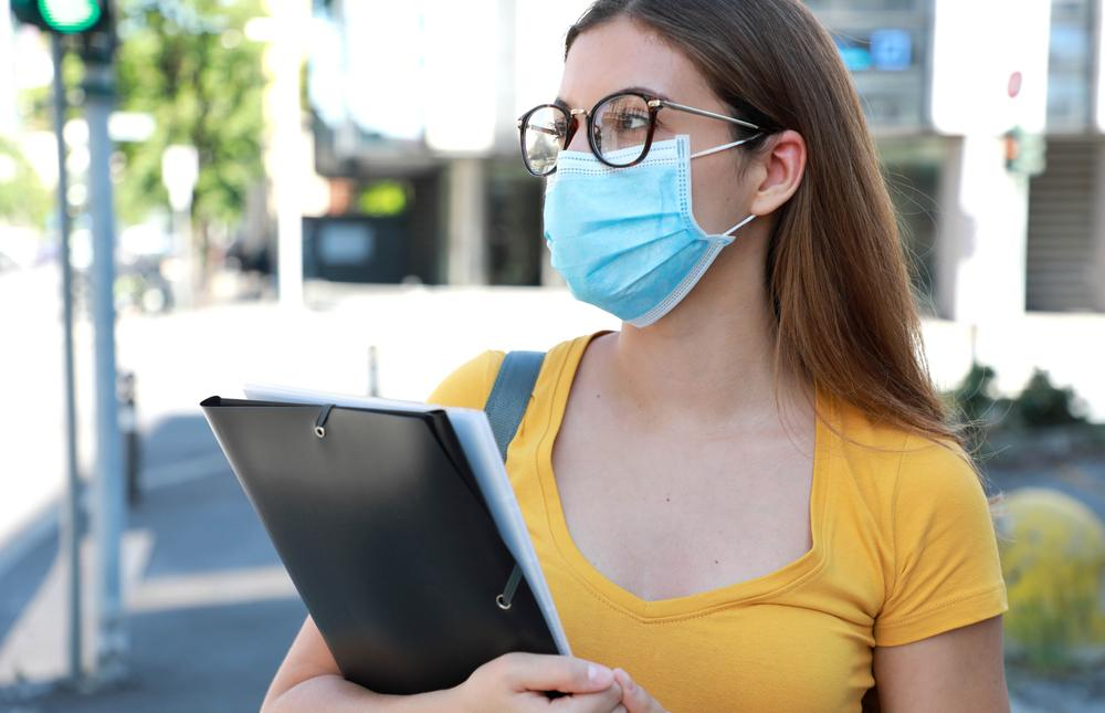 student walking outside carrying books and wearing a face mask