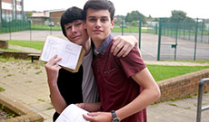 Two students posing with their exam results