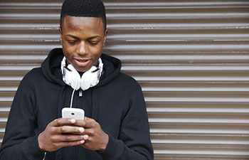 Student with headphones looking at his mobile phone
